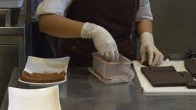 Kobieta robić kakaowy proszek spada odsiew na czekoladowych barach i układa puszek zbiory