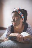 Kobieta robi borowinowy twarzowemu maskujący w domu zdrój Zdjęcia Stock