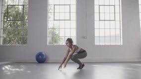 Kobieta robi burpee treningowi przy sprawności fizycznej studiiem zbiory