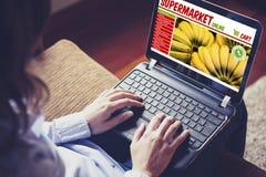 Kobieta robi jej sklepu spożywczego zakupy internetem z laptopem przy ho zdjęcie stock