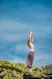 Kobieta robi joga ćwiczeniu na świeżym powietrzu z niebieskim niebem Obrazy Royalty Free