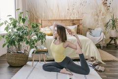 Kobieta robi joga ćwiczeniu w jej lekkiej eleganckiej sypialni w domu Ranku trening w sypialni Zdrowy i sport styl życia Obraz Stock