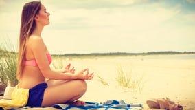 Kobieta robi joga na piaskowatej plaży Zdjęcia Royalty Free
