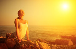 Kobieta robi joga na plaży przy zmierzchem Obraz Stock