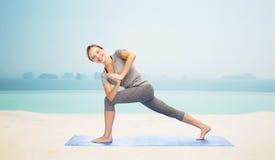 Kobieta robi joga niskiemu kątowi lunge pozę na macie Obrazy Stock