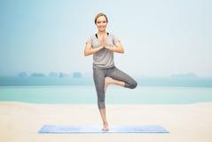 Kobieta robi joga w drzewnej pozie na macie Zdjęcie Royalty Free