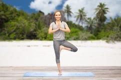 Kobieta robi joga w drzewnej pozie outdoors na plaży fotografia royalty free