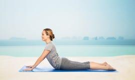 Kobieta robi joga w psiej pozie na macie Zdjęcie Royalty Free