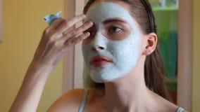 Kobieta robi kosmetyk masce na jej twarzy zbiory