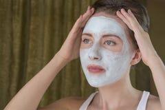 Kobieta robi kosmetyk masce na jej twarzy zdjęcie stock