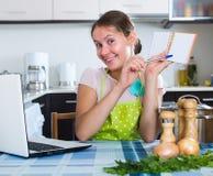 Kobieta robi liście zakupów przy kuchnią Obraz Royalty Free