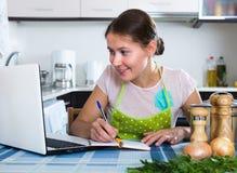 Kobieta robi liście zakupów przy kuchnią Zdjęcie Royalty Free