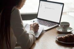 Kobieta robi notatkom czyta emaila list na laptopie w kawiarni zdjęcie stock
