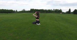 Kobieta robi pilates i jog podczas gdy siedzący na trawie Round widok zdjęcie wideo
