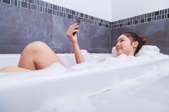 Kobieta robi selfie fotografii w wannie w łazience Obrazy Stock
