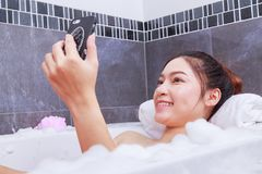 Kobieta robi selfie fotografii w wannie w łazience Fotografia Royalty Free