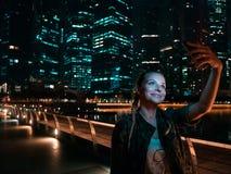Kobieta robi selfie z drapacza chmur tłem przy nocą zdjęcia royalty free