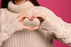 Kobieta robi sercu z jej rękami na koloru tle zdjęcie stock