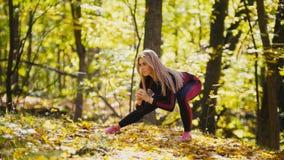 Kobieta robi sprawności fizycznej ćwiczy plenerowego Żeński rozciąganie w jesień lasu schudnięcia dziewczynie przy treningiem - k Zdjęcie Royalty Free