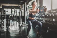 Kobieta robi treningowi z ciężaru talerzem przy gym obraz royalty free