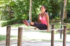 Kobieta robi upadom ćwiczy na równoważenie barze w parku Zdjęcie Royalty Free