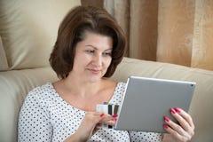 Kobieta robi zakupowi w internecie kart? kredytow? zdjęcie stock