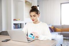 Kobieta robi zakupy online z jej kartą kredytową podczas gdy siedzący przed laptopem obrazy stock