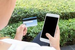 Kobieta robi zakupy online z smartphone wewnątrz relaksuje parka Fotografia Royalty Free