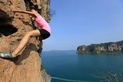 Kobieta rockowego arywisty pięcie przy nadmorski góry skałą Zdjęcia Stock