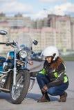 Kobieta rowerzysta próbuje naprawiać mieszkanie na motocyklu przy miasto drogą fotografia stock
