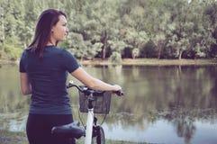 Kobieta rowerzysta w parku z wodnym odbiciem fotografia royalty free