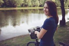 Kobieta rowerzysta w parku z wodnym odbiciem obrazy royalty free