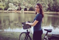 Kobieta rowerzysta w parku z wodnym odbiciem zdjęcie royalty free