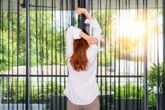 Kobieta rozciąga ona ręki podczas gdy trwanie i przyglądający wschód słońca thr zdjęcie stock