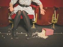 Kobieta rozlewa jej popkorn w kinie Obrazy Royalty Free