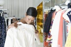 Kobieta Rozważa Białą kurtkę W ubrania sklepie zdjęcia stock