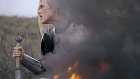 Kobieta rycerz opiera przeciw kordzika obsiadaniu spojrzeniami i ogieniem wokoło, zwolnione tempo zbiory