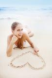Kobieta rysuje kierowego znaka na piasku Obraz Stock