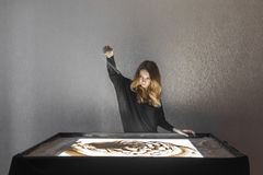 Kobieta rysuje na piasku, piasek animacja, piasek nalewa od jego ręk Zdjęcia Stock