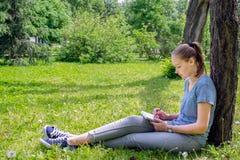 Kobieta rysuje obsiadanie na trawie Obraz Royalty Free