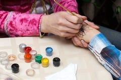 kobieta rysuje pająka na dziewczyny ręce Obraz Stock