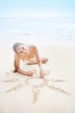 Kobieta rysuje słońce znaka na piasku Zdjęcie Royalty Free