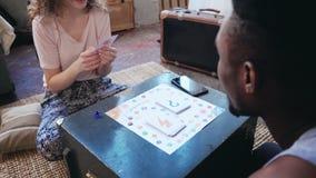 Kobieta rzuca kostka do gry i wp8lywy kartę Obsługuje wp8lywy jej remisy i ręka palec Wieloetniczna para bawić się knur grę zbiory wideo
