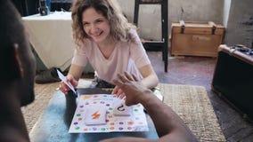 Kobieta rzuca kostka do gry i wp8lywy kartę Obsługuje wp8lywy jej remisy i ręka palec Wieloetniczna para bawić się knur grę Zdjęcie Stock