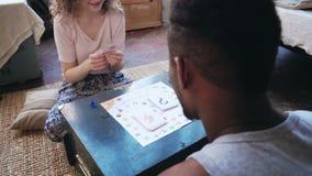 Kobieta rzuca kostka do gry i wp8lywy kartę Obsługuje wp8lywy jej remisy i ręka palec Wieloetniczna para bawić się knur grę Fotografia Stock
