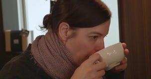 Kobieta sączy kawę jako kamer niecki wokoło ona zbiory