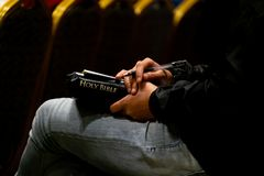 Kobieta Słucha egzorta i Pisać Coś na papierze z biblią fotografia royalty free