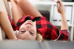 Kobieta słucha muzycznego kłamstwo na kanapie fotografia stock