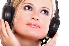 Kobieta słucha muzyczny biały tło z hełmofonami obrazy royalty free
