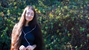 Kobieta słucha muzykę na z długie włosy w hełmofonach pogodnym, wietrznym dniu, zdjęcie wideo